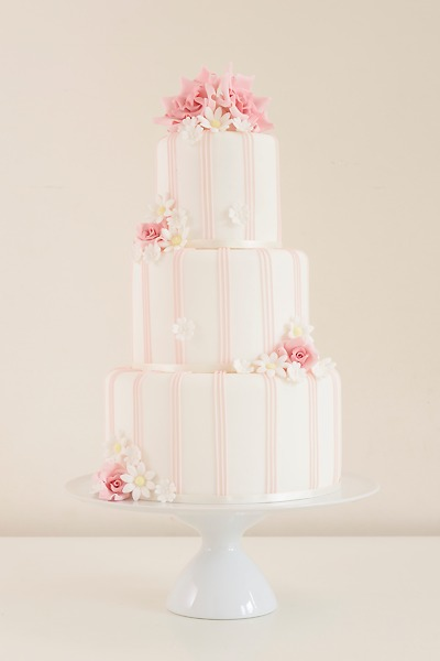 Becca  Palest candy pink stripes combine with pink roses and daisies in this wedding cake that's perfect for a summer's day.