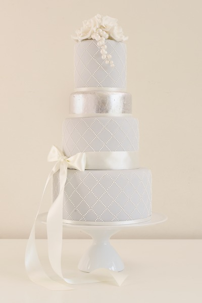 Kate Formal and elegant in soft sugarpaste with restrained royal icing piped details. This cake can be colour-adapted to your theme.