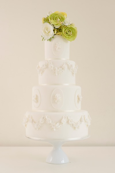 Tanya Imposing in white on white with sculptural floral details. This cake was made to take centre stage.